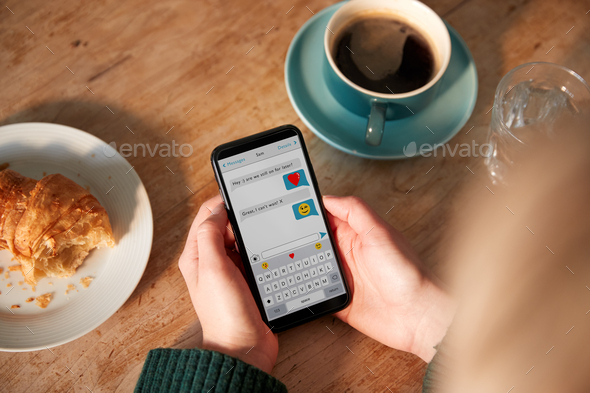 Close Up Of Woman Looking At Messages Arranging Romantic Date On Mobile Phone Messaging App In Cafe - Stock Photo - Images