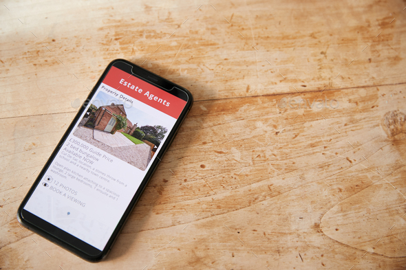 Close Up Of Mobile Phone With Realtors Property App Lying On Table - Stock Photo - Images