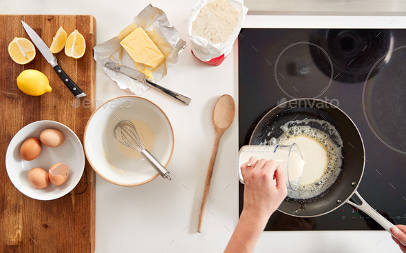 Overhead Shot Of Woman In Kitchen Pouring Batter Into Pan For Pancakes Or Crepes For Pancake Day - Stock Photo - Images