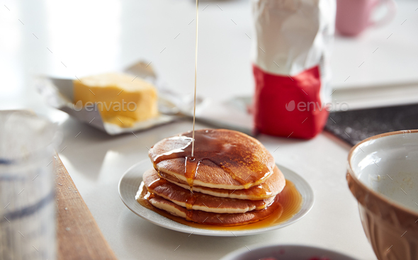 Maple Syrup Being Poured On Stack Of Freshly Made Pancakes Or Crepes On Table For Pancake Day - Stock Photo - Images