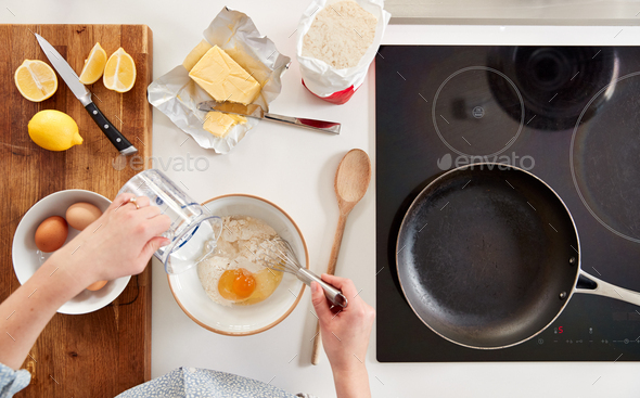 Overhead Shot Of Woman In Kitchen Mixing Ingredients For Pancakes Or Crepes For Pancake Day - Stock Photo - Images