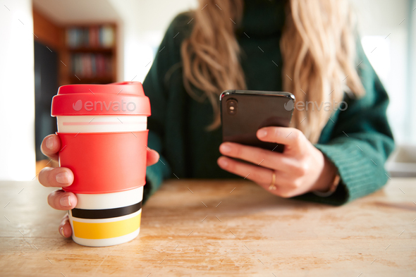 Close Up Of Woman Using Mobile Phone With Reusable Takeaway Drink Cup Sitting At Table  In Cafe - Stock Photo - Images