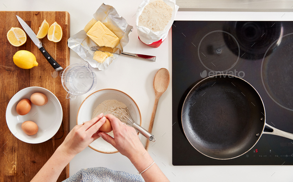 Overhead Shot Of Woman In Kitchen With Ingredients Making Pancakes Or Crepes For Pancake Day - Stock Photo - Images