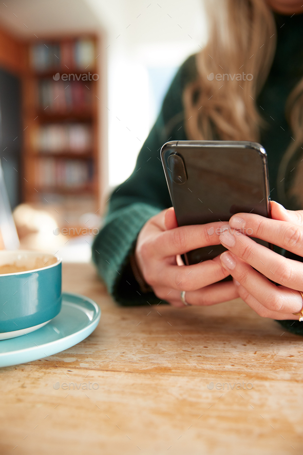 Close Up Of Woman Using Mobile Phone Sitting At Table  In Cafe - Stock Photo - Images