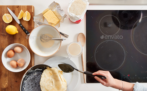 Overhead Shot Of Woman In Kitchen Serving Pancakes Or Crepes For Pancake Day - Stock Photo - Images