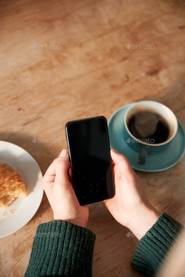 Close Up Of Woman Looking At Blank Screen With Copy Space On Mobile Phone  In Cafe - Stock Photo - Images