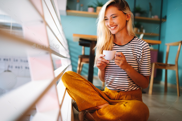 Beautiful woman drinking coffee in the morning sitting by the window - Stock Photo - Images