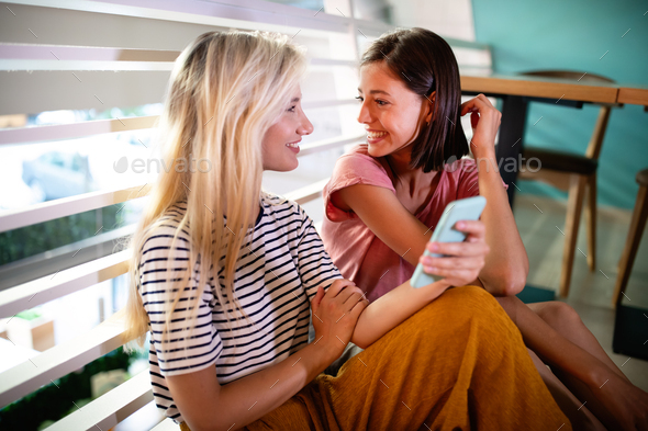 Beautiful young women friends using smart phone together and having fun - Stock Photo - Images