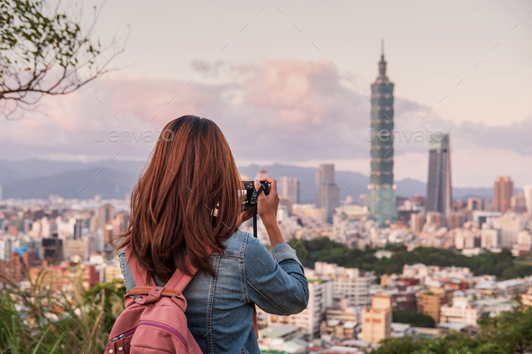 Young woman traveler taking photo of beautiful cityscape - Stock Photo - Images