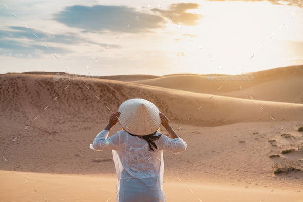 Young woman traveler looking sunset at red sand dunes in Vietnam, Travel lifestyle concept - Stock Photo - Images