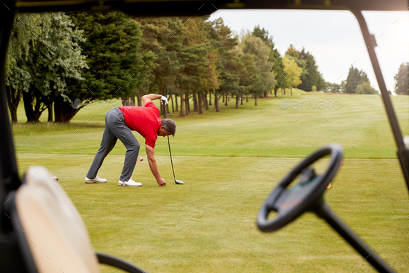 Mature Male Golfer Preparing To Hit Tee Shot Along Fairway With Driver Viewed Through Buggy Window - Stock Photo - Images
