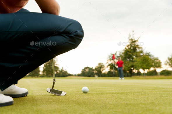 Close Up Of Female Golfer Lining Up Shot On Putting Green As Man Tends Flag - Stock Photo - Images