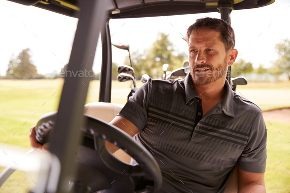 Mature Man Playing Golf Driving Buggy Along Course To Green On Red Letter Day - Stock Photo - Images