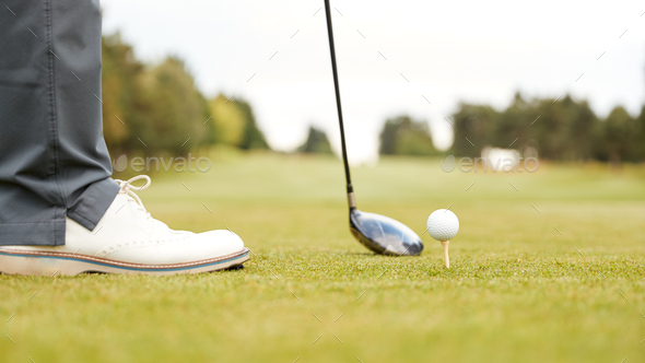 Close Up Of Mature Male Golfer Preparing To Hit Tee Shot Along Fairway With Driver - Stock Photo - Images