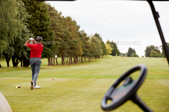 Mature Male Golfer Hitting Tee Shot Along Fairway With Driver Viewed Through Buggy Window - Stock Photo - Images