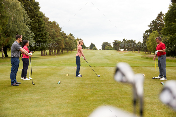 Golf Professional Demonstrating Tee Shot To Group Of Golfers During Lesson - Stock Photo - Images