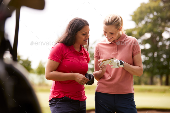 Two Women Playing Golf Marking Scorecard With  Buggy In Foreground - Stock Photo - Images