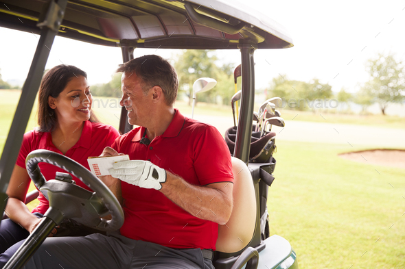 Mature Couple Playing Golf Marking Scorecard In Buggy Driving Along Course - Stock Photo - Images