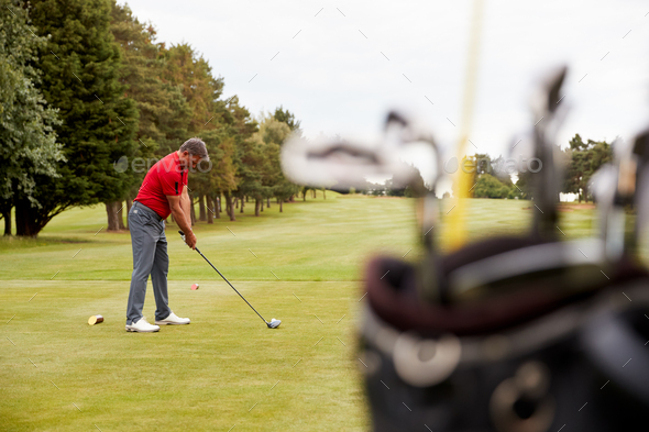 Mature Male Golfer Preparing To Hit Tee Shot Along Fairway With Bag Of Clubs In Foreground - Stock Photo - Images