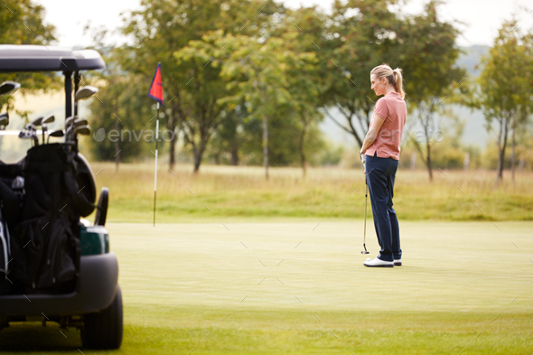 Rear View Of Woman Getting Out Of Golf Buggy To Play Shot On Green - Stock Photo - Images