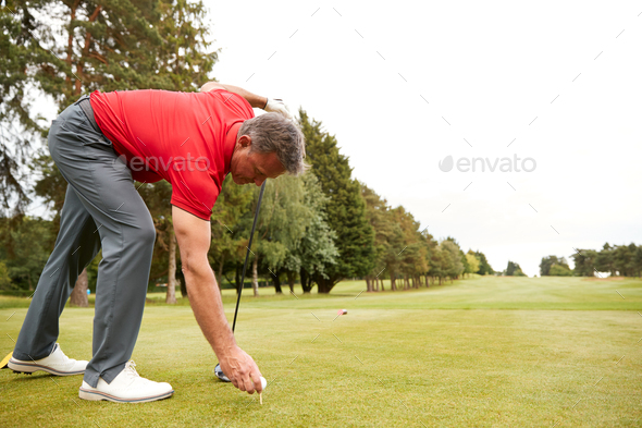 Mature Male Golfer Preparing To Hit Tee Shot Along Fairway With Driver - Stock Photo - Images