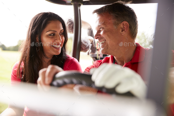 Mature Couple Playing Golf Driving Buggy Along Course To Green On Red Letter Day - Stock Photo - Images
