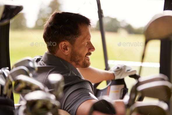 Rear View Of Mature Man Playing Golf Driving Buggy Along Course Viewed Through Golf Clubs - Stock Photo - Images