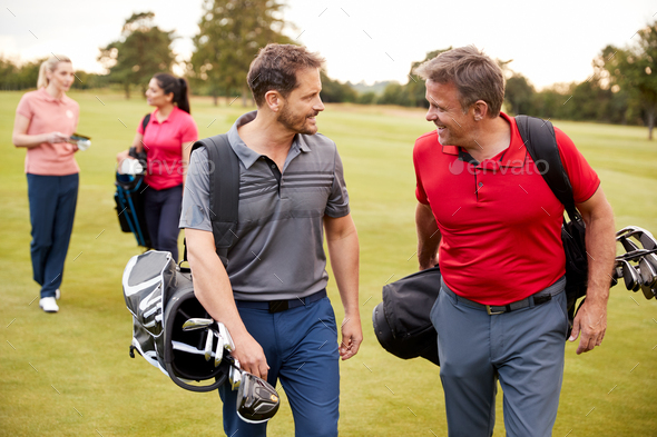 Two Mature Couples Playing Round Of Golf Carrying Golf Bags Along Fairway - Stock Photo - Images