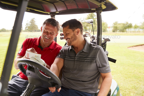 Two Mature Men Playing Golf Marking Scorecard In Buggy Driving Along Course - Stock Photo - Images