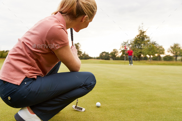 Female Golfer Lining Up Shot On Putting Green As Man Tends Flag - Stock Photo - Images
