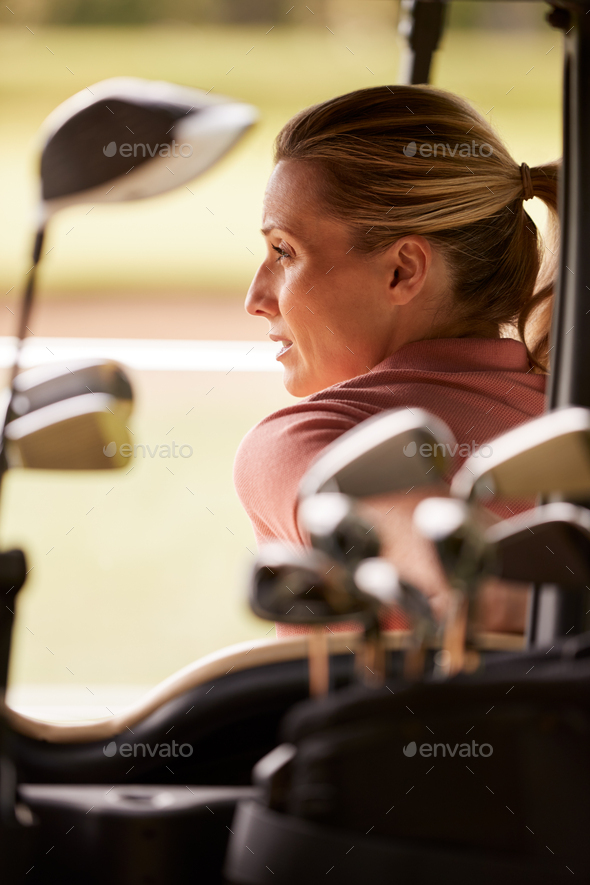 Rear View Of Mature Woman Playing Golf Driving Buggy Along Course Viewed Through Golf Clubs - Stock Photo - Images