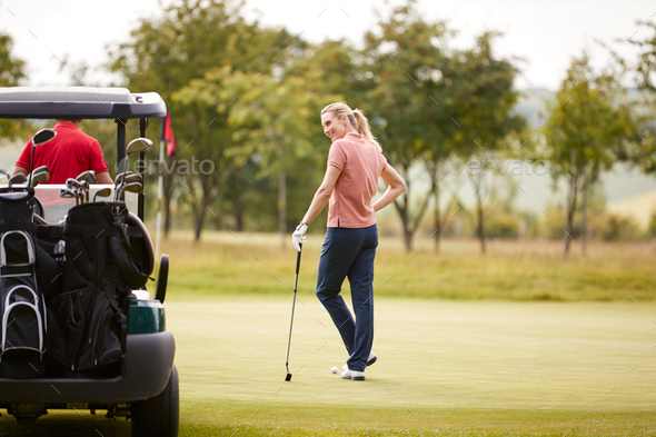 Rear View Of Couple Getting Out Of Golf Buggy To Play Shot On Green - Stock Photo - Images