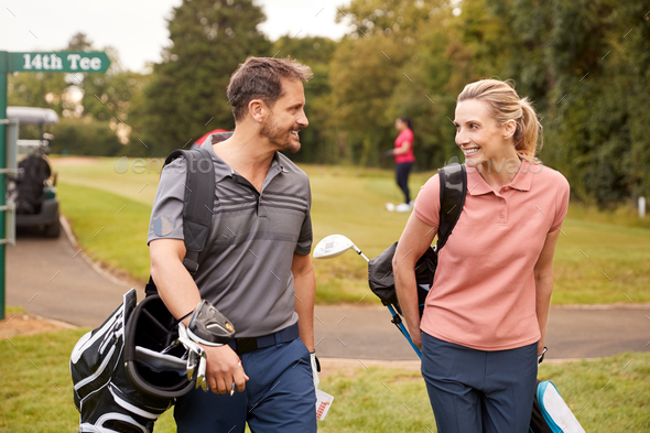 Mature Couple Playing Round Of Golf Carrying Golf Bags And Talking - Stock Photo - Images