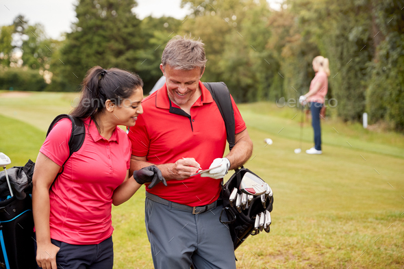 Mature Couple Playing Round Of Golf Carrying Golf Bags And Marking Scorecard - Stock Photo - Images