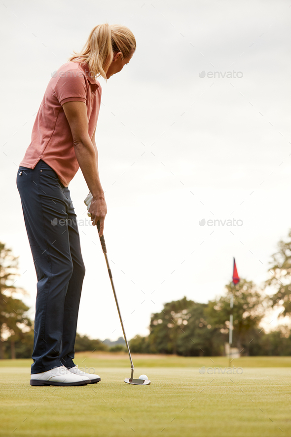 Rear View Of Female Golfer Putting Ball On Green - Stock Photo - Images