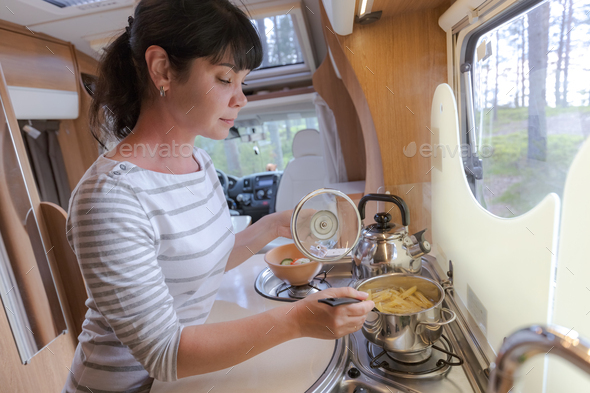 Woman cooking in camper, motorhome interior - Stock Photo - Images