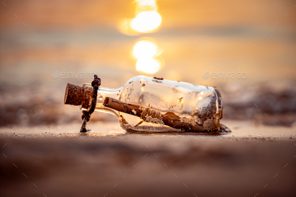 Message in the bottle against the Sun setting down - Stock Photo - Images