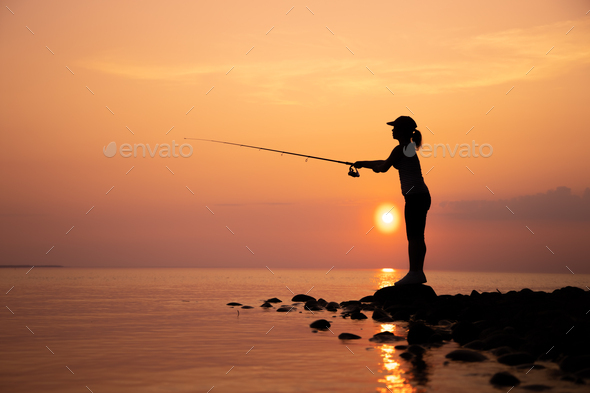 Woman fishing on Fishing rod spinning in Norway. - Stock Photo - Images