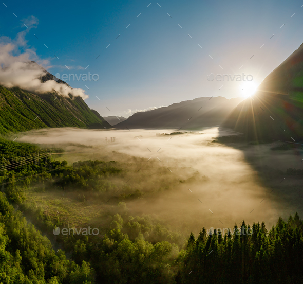 Morning mist over the valley among the mountains in the sunlight. - Stock Photo - Images