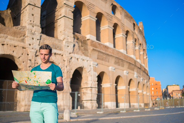 Happy guy with map in front of Colosseum. Young man searching the attraction background the famous - Stock Photo - Images