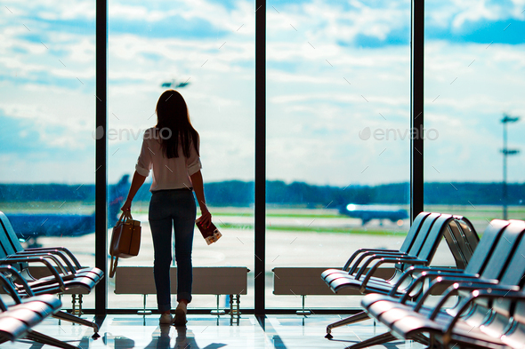 Young woman in international airport with her luggage background big window. Airline passenger in an - Stock Photo - Images