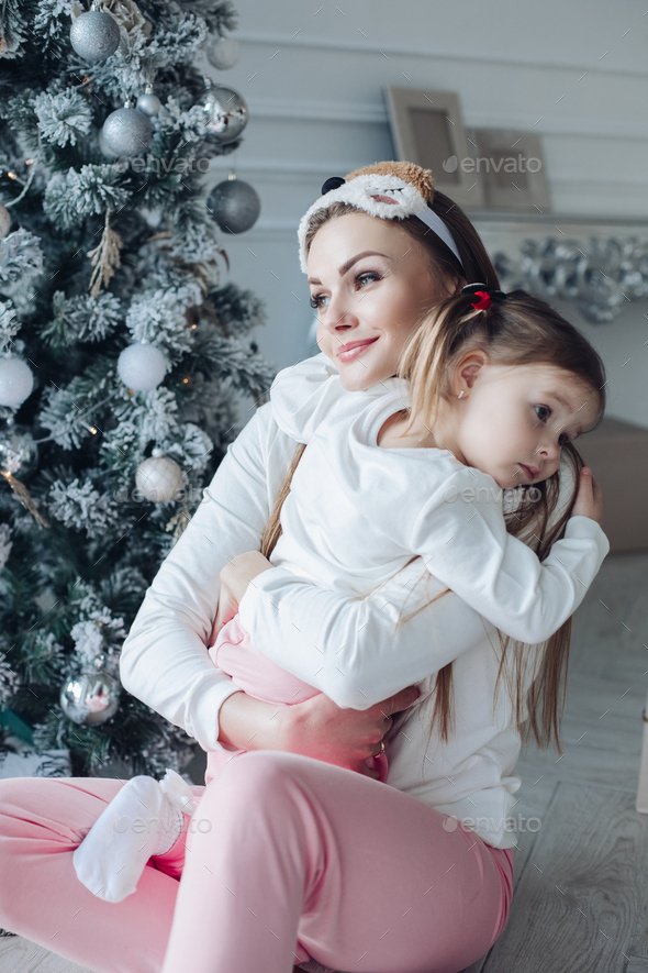 Happy festive mother and daughter hugging sitting together at decorating beautiful Christmas tree - Stock Photo - Images