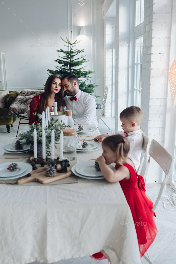 Happy young family sitting at the festive table at home - Stock Photo - Images