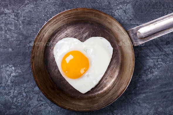 Fried egg in heart shape.Holiday Breakfast.Valentin Day. - Stock Photo - Images