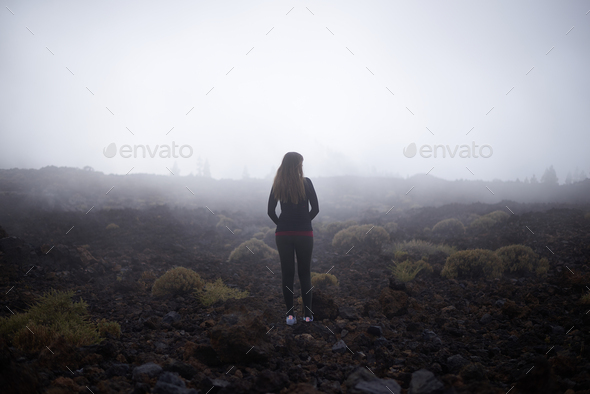 Young woman contemplating the fog on her way to Teide top in Tenerife, Spain - Stock Photo - Images