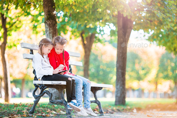 Little adorable girls with smartphone in fall outdoors. Kids having fun at warm sunny day in autumn - Stock Photo - Images