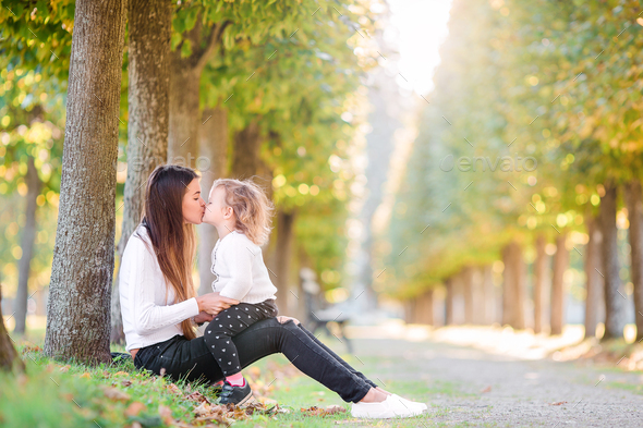 Family of mother and little kid outdoors in park at autumn day - Stock Photo - Images