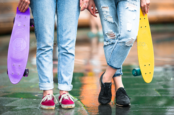 Two hipster girls with skateboard outdoors in sunset light. Closeup skatebords in female hands - Stock Photo - Images