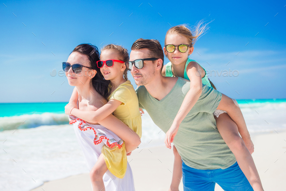 Happy beautiful family of four on beach on vacation - Stock Photo - Images