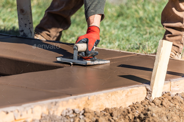 Construction Worker Using Hand Groover On Wet Cement Forming Coping Around New Pool - Stock Photo - Images